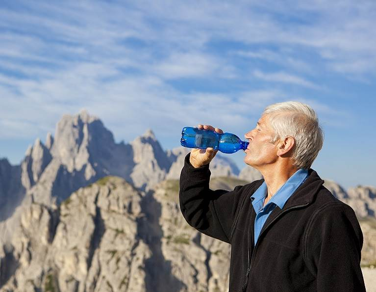 Man drinking water on a mountain from a plastic water bottle.